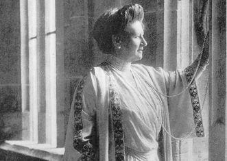 Queen Charlotte in simple clothing, standing by a window, circa 1920 in Bebenhausen Palace; scan: Landesmedienzentrum Baden-Württemberg, credit unknown#